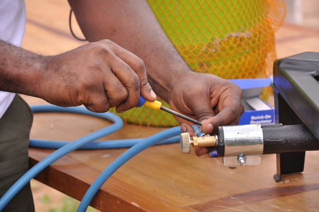 A GTHI volunteer sets up a gas burner
